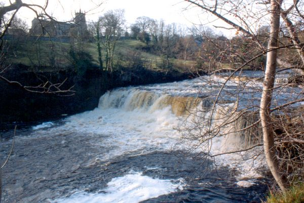 Aysgarth Falls Middle Drop Waterfall with St. Andrews Church on the horizon.